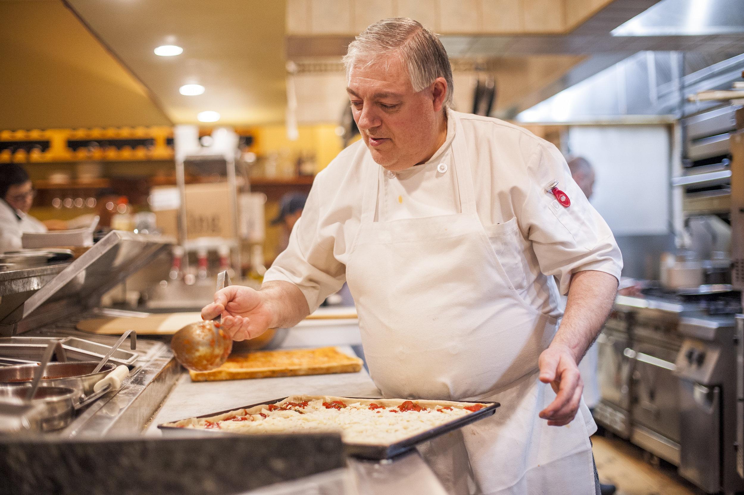 Vito DeFeo, owner of Viajo's Restaurant in Huntington, assembles a pizza.