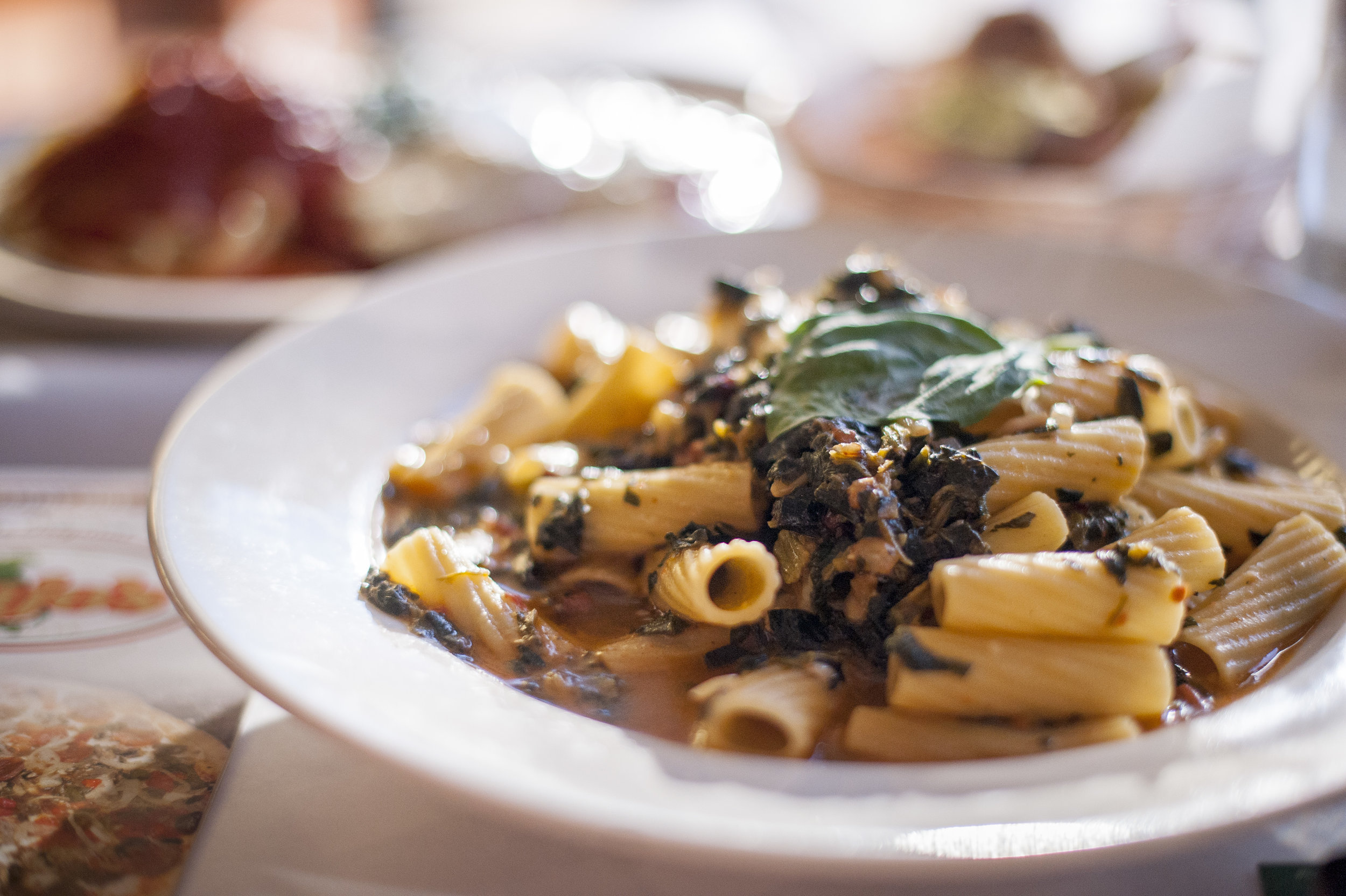 Rigatoni Alla Viajo's plates a chewy rigatoni pasta in a pomodoro white wine sauce with onions, raisins, spinach and pigtail nuts, coming together to marry the worlds of sweet, savory and nutty.