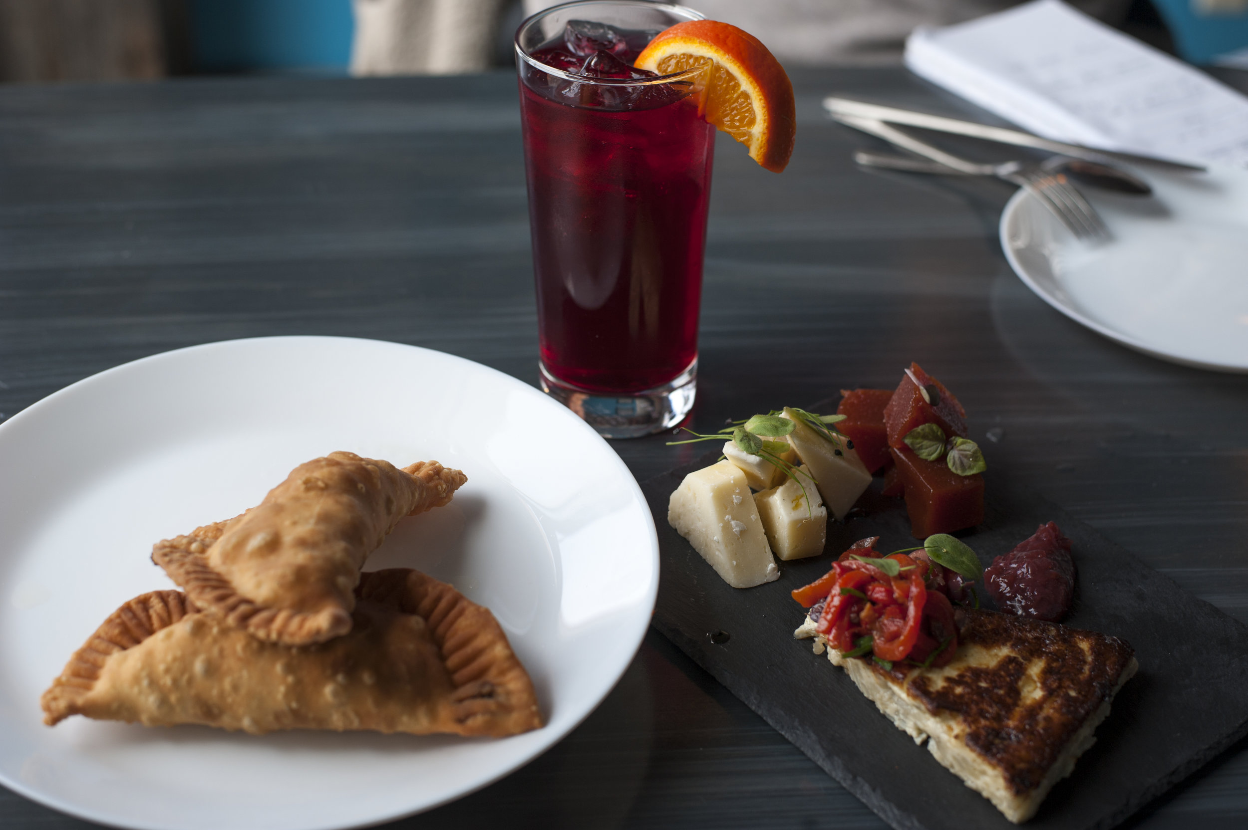 Classic baked Empanadas are shown with the Guava Plate, a medley of sweet and savory sensations, alongside a non-alcoholic refreshing sangria.