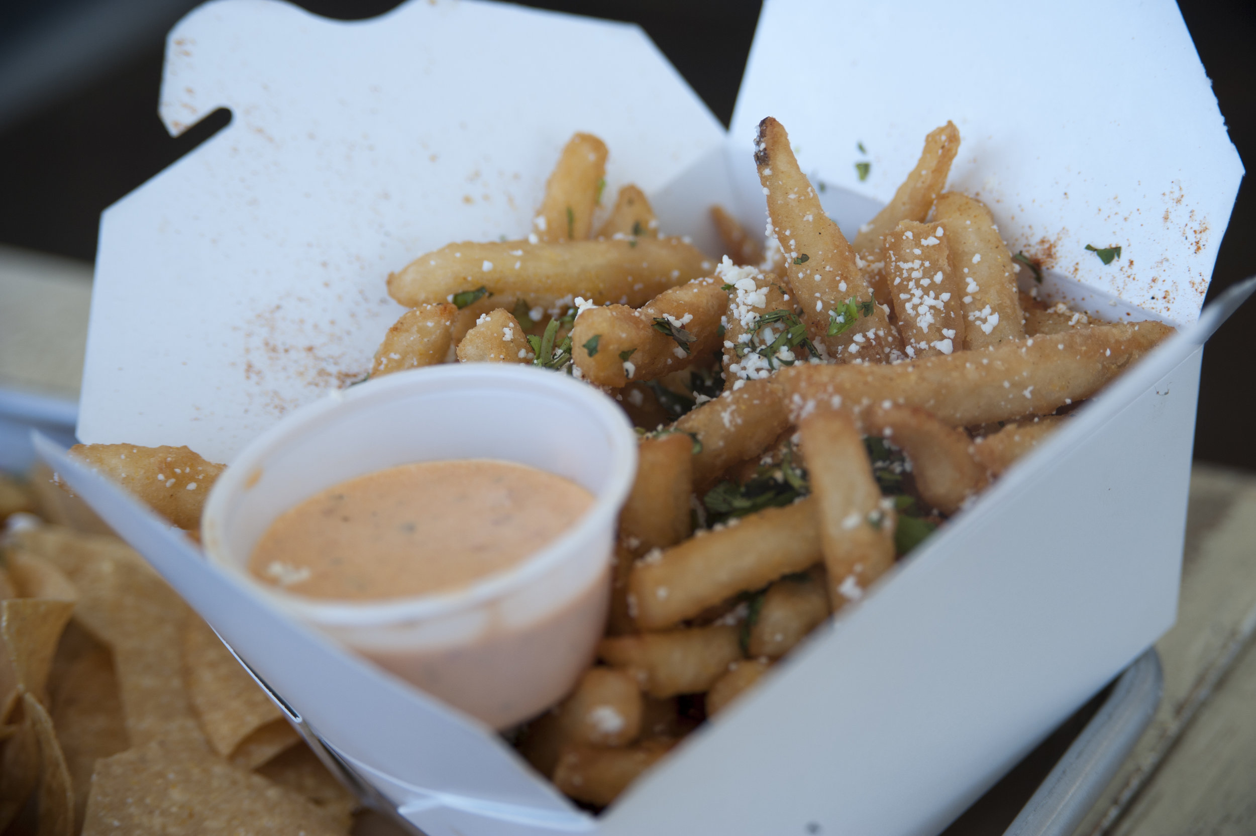 The Street Fries offers crispy fries topped with cotija, sea salt, cilantro and tajin, a Mexican seasoning, alongside the signature Whale Sauce.