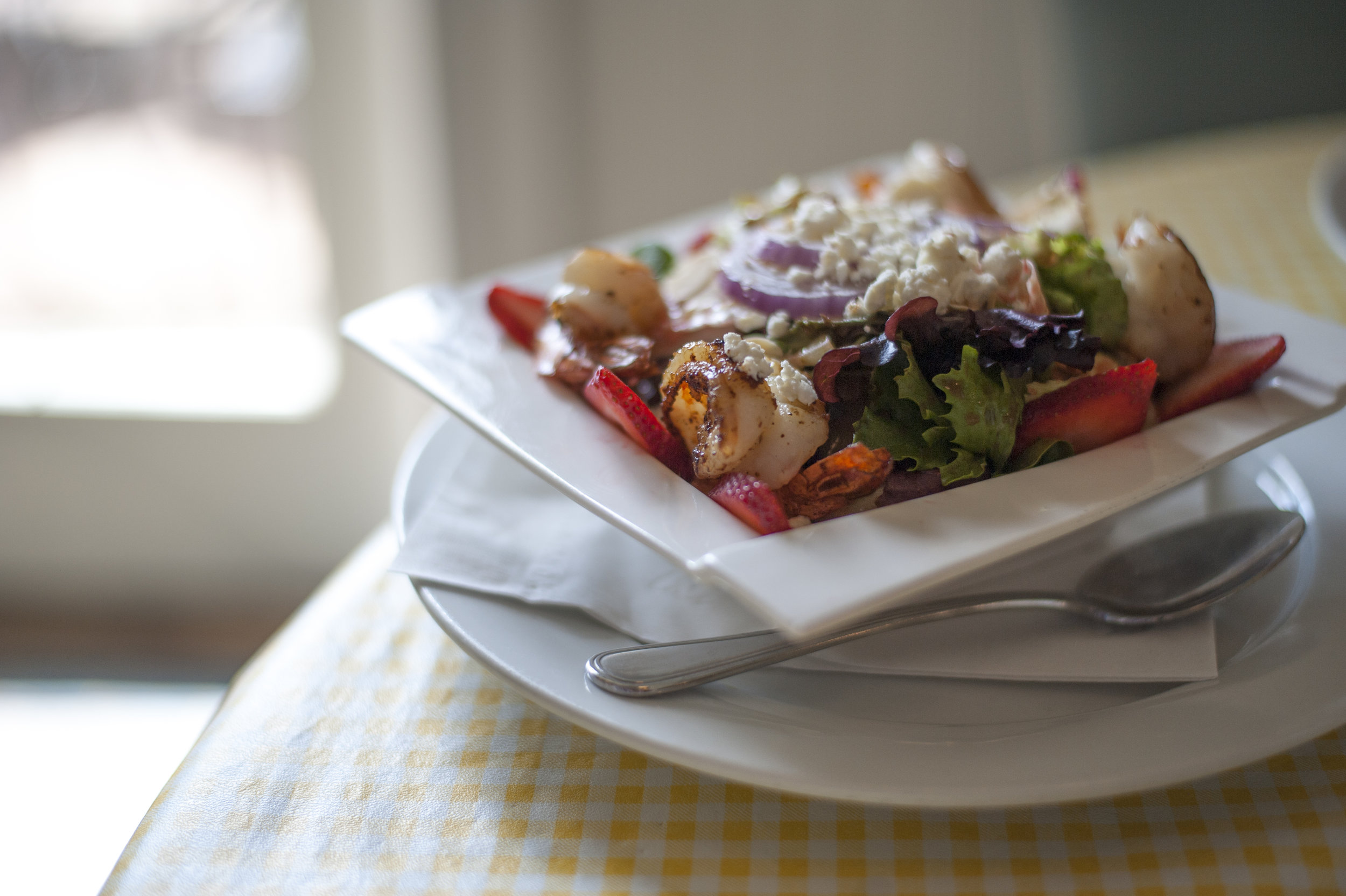 The Summer Strawberry & Shrimp Salad tosses together char-grilled shrimp over mixed greens, freshly sliced strawberries, goat cheese, sliced almonds and red onion with a raspberry vinaigrette.