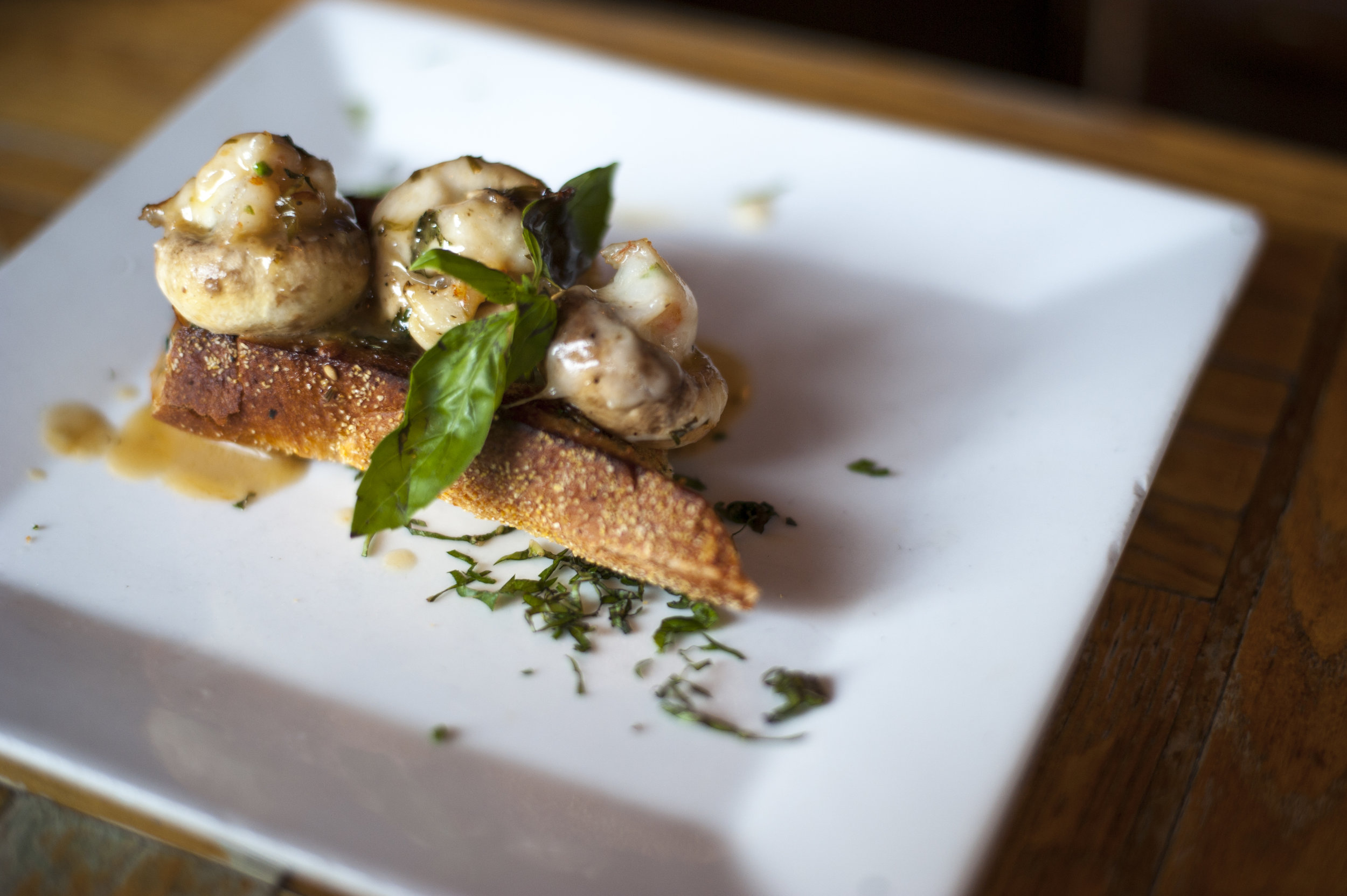 The Shrimp Cargot is drizzled with garlic lemon sauce, serving up deliciously savory shrimp stuffed into a mushroom, atop a country bread crostini.