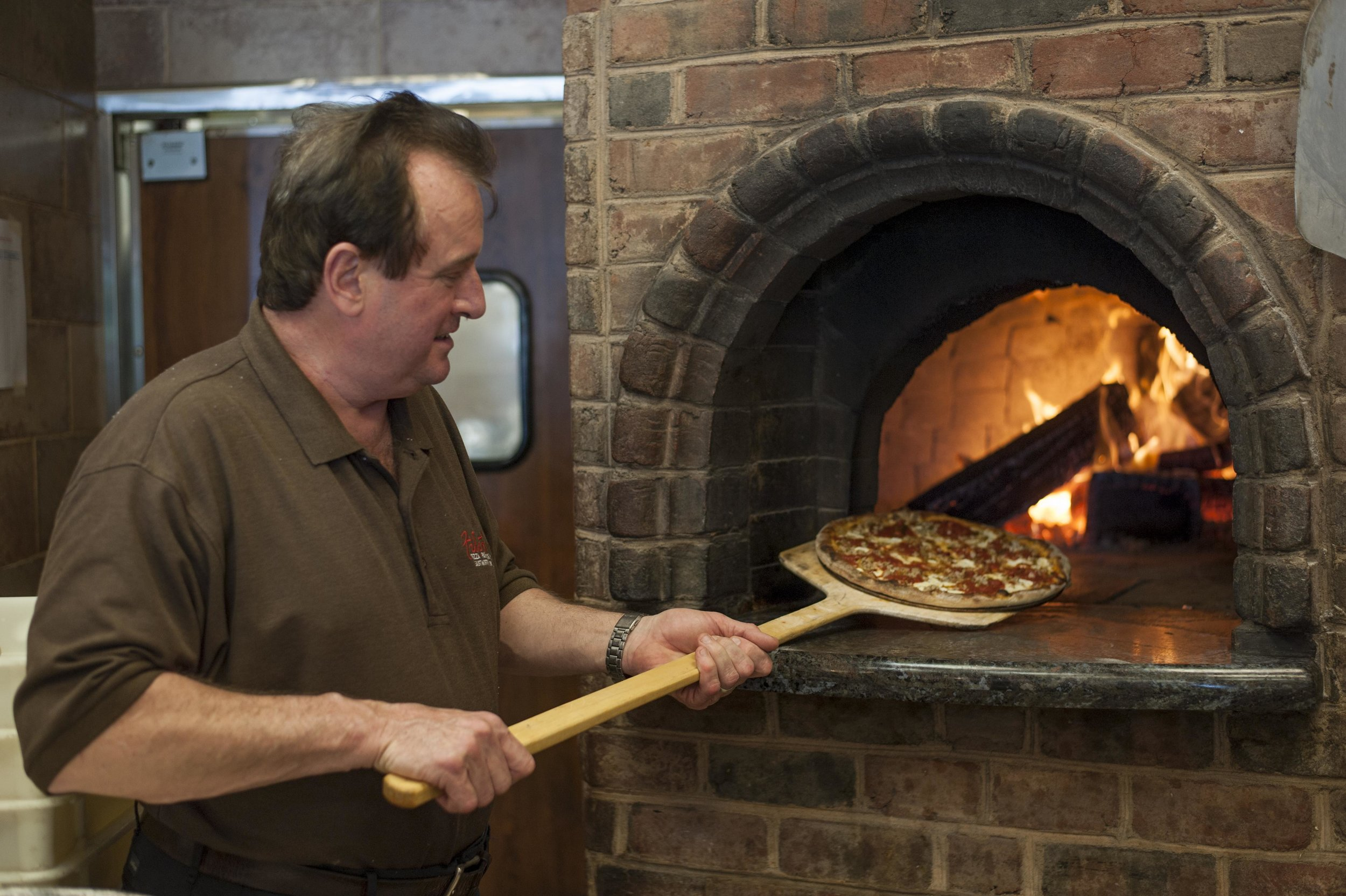 Long Islander News photos/David Weber  Rich Braue, co-owner of Filetto's ristorante and head chef with more than 40 years of culinary expertise, puts in a pizza into the establishment's renowned brick oven.