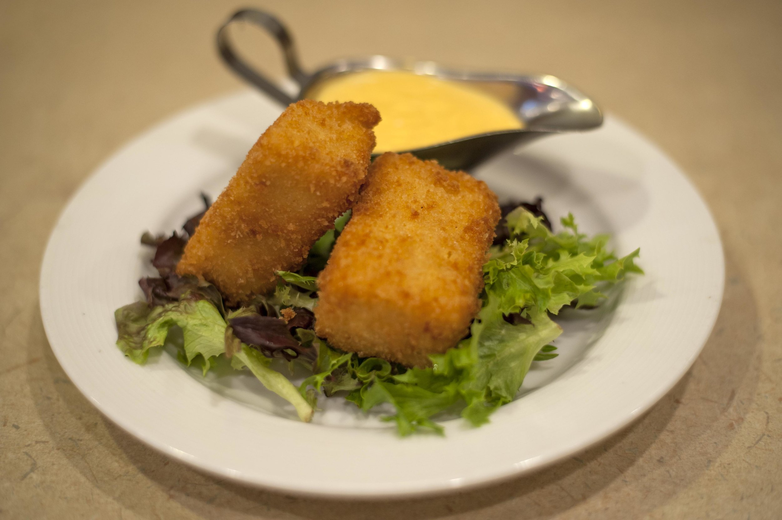 The Deep Fried Mac 'n' Cheese features a wholesome helping of mac 'n' cheese, deep fried to crispy perfection with a side of cheddar cheese sauce.