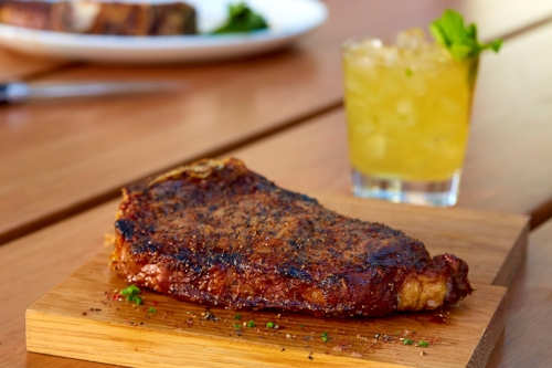 Make dad feel like a king this Father's Day with an 18-ounce, 28-day Bone-In Dry-Aged Strip Steak, above, paired with a Gentleman's Mule, inset, made with Basil Hayden's Aged Bourbon courtesy of Del Frisco's Grille in Huntington Station.