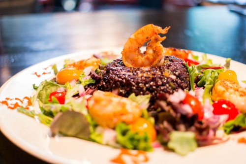 The Drunken Shrimp and Black Voodoo Rice Salad tosses up grilled, mildly-heated Gulf shrimp soaked in cucumber with black voodoo rice in a Thai sesame dressing, with a side of mixed greens.