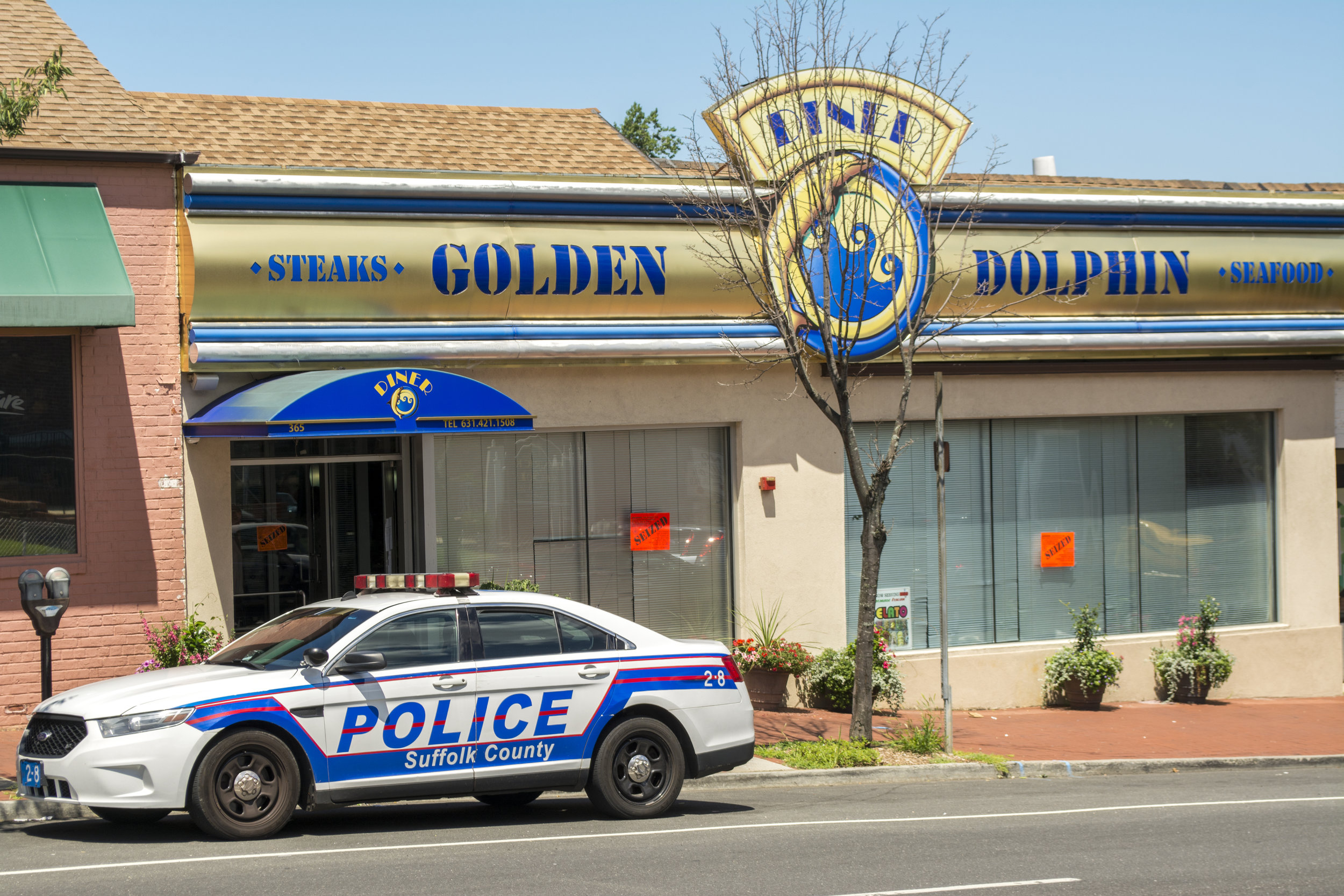 A Suffolk police officer's vehicle is pictured outside the Golden Dolphin diner Wednesday afternoon after it was seized by the state over apparent unpaid taxes.   Photo by  Long Islander News photo/Paul Shapiro