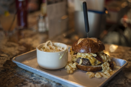 The Mac Attack burger topped with bacon and succulent mac and cheese between a warm pretzel bun.