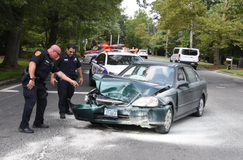 Suffolk police officers survey damage to one car involved in a two-car crash in Melville on Saturday.  Photo by Steve Silverman