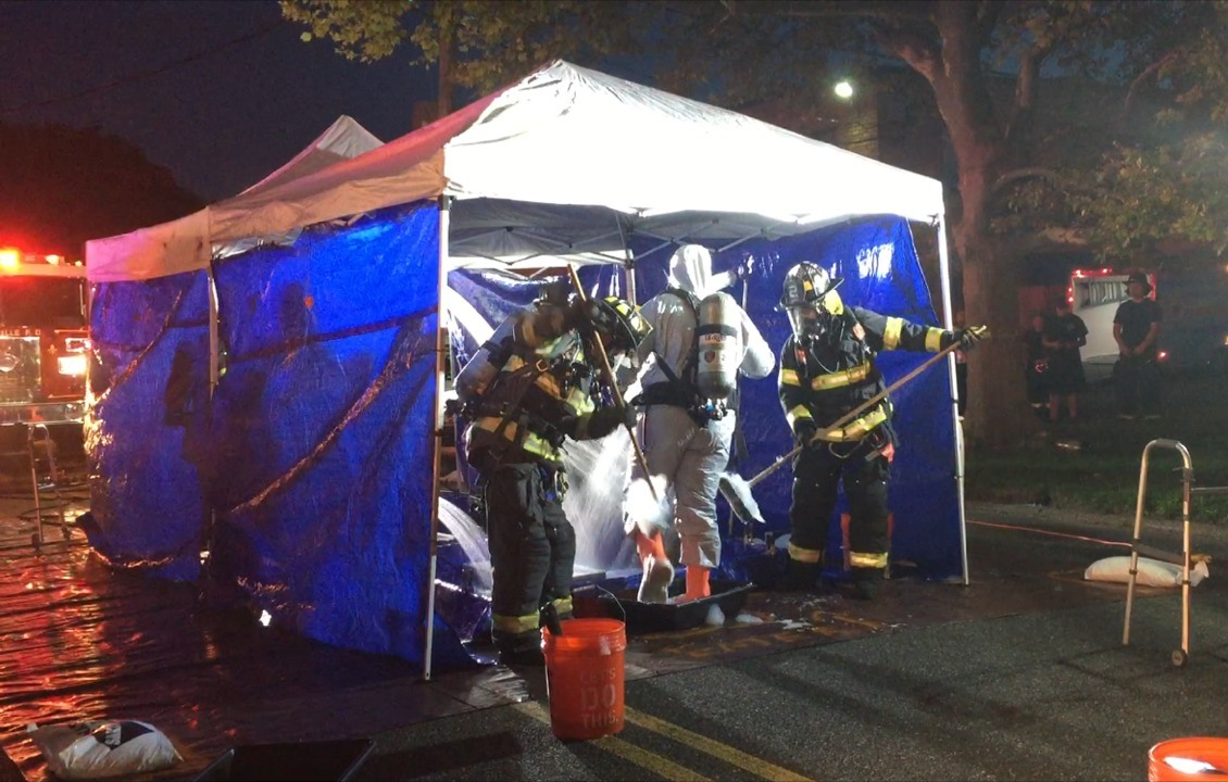 Hazmat-equipped workers neutralize a sulfuric acid spill in East Farmingdale last Thursday.  Photos Courtesy of Melville FD