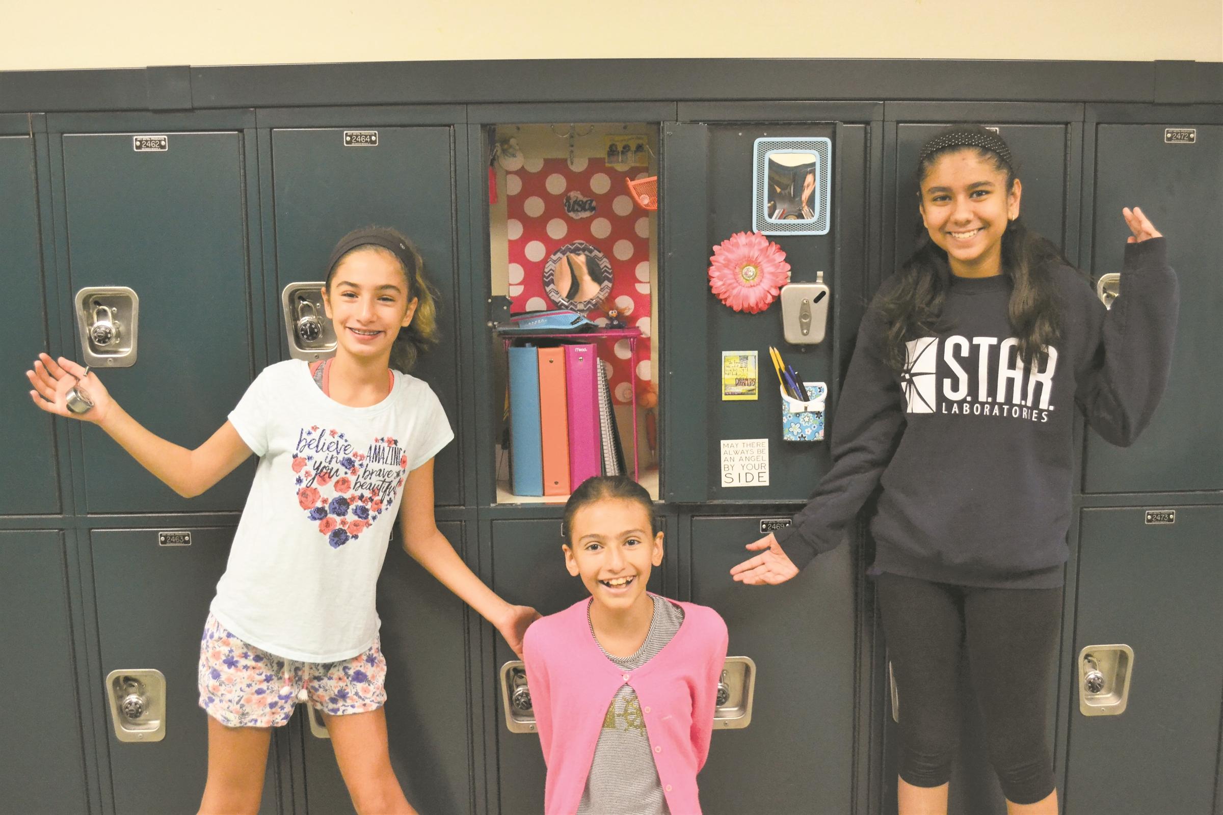 Harborfields seventh graders Gabby Dimartino, Alexa Palacios and Arya Sharma set up their Oldfield Middle School lockers on Tuesday.   Photo/Harborfields School District