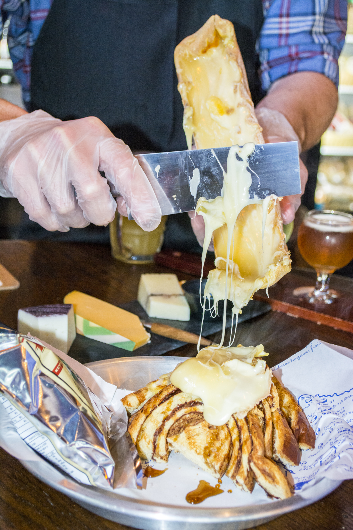 Brew Cheese owner David Striffler scrapes melted raclette cheese onto the French Toast Sandwich ($10)   Long Islander News photos/Barbara Fiore
