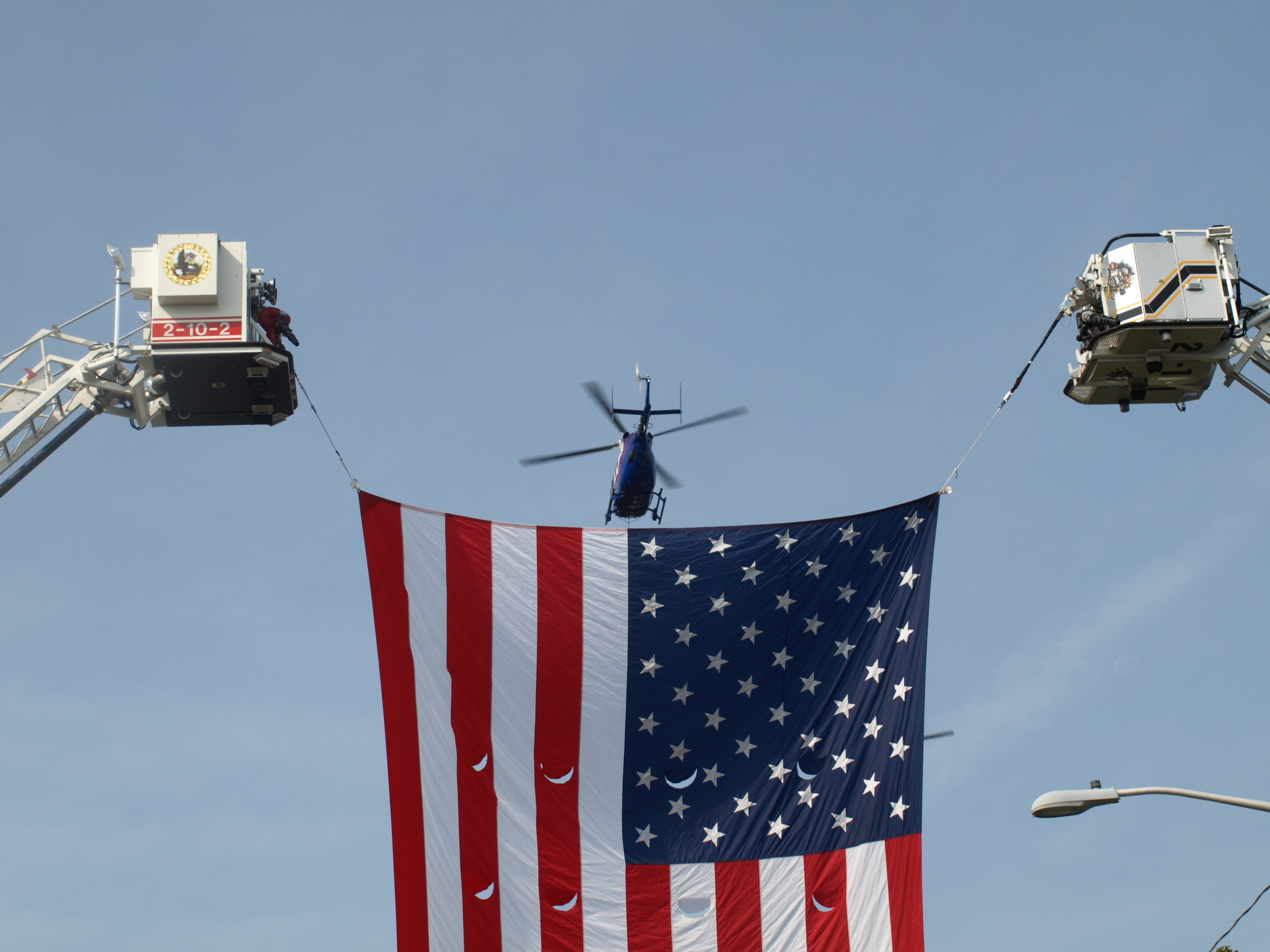 A Suffolk County Police Department helicopter flies over the ceremony.   Long Islander News photos/Connor Beach