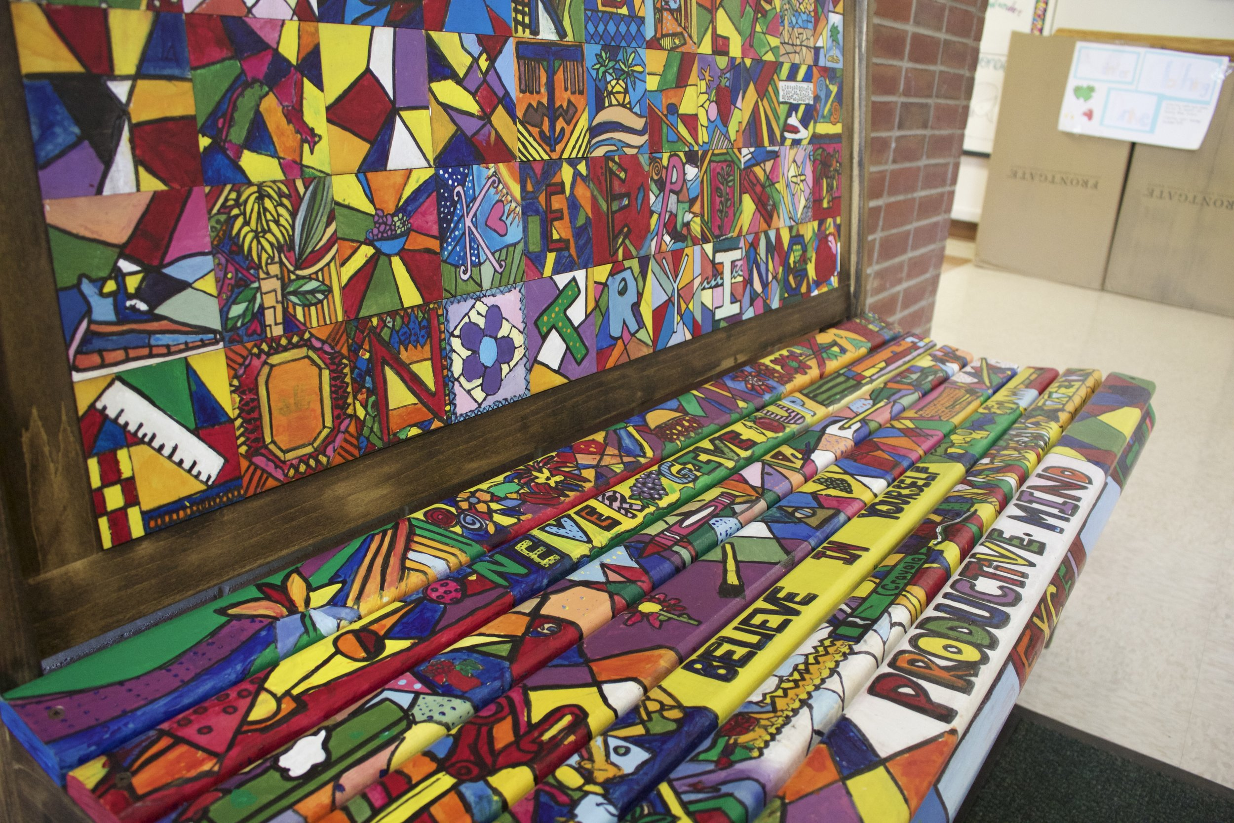 This colorful Romero Britto-inspired bench was installed at West Side School as a way to remind students to show kindness and represent grit.   Long Islander News Photo/Janee Law