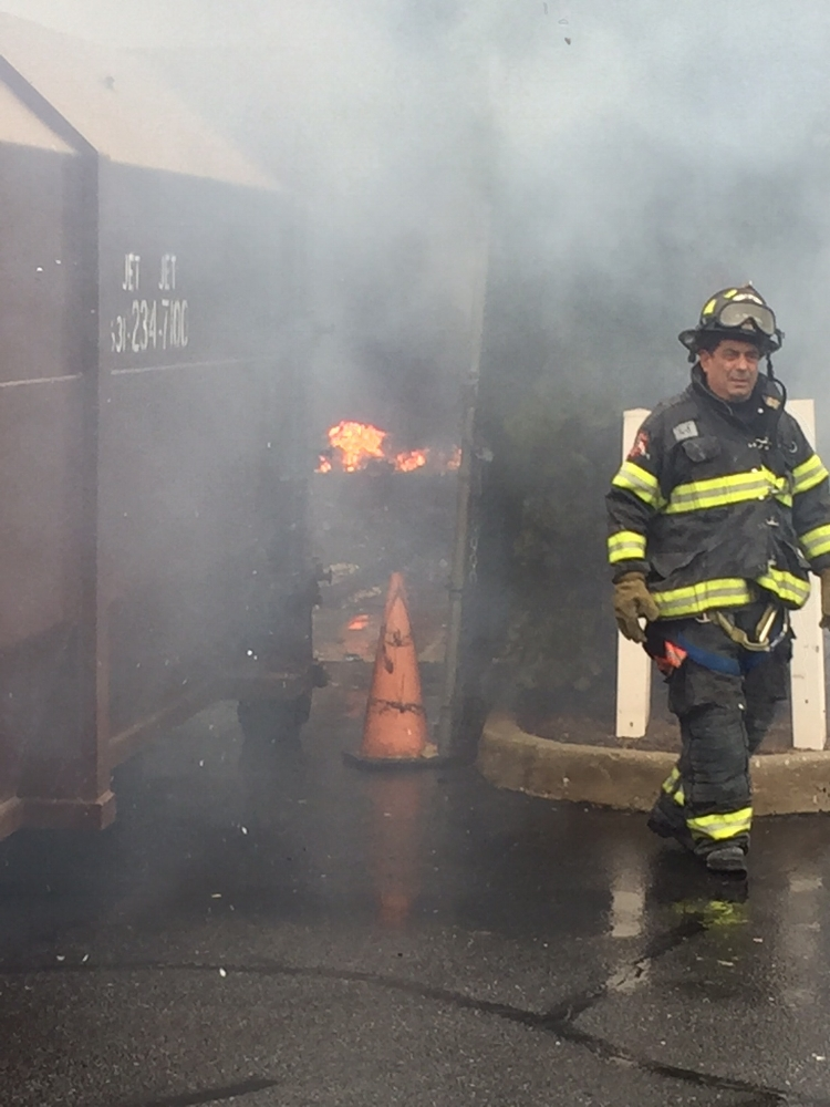 Firefighters battle a blaze that originated in a trash compactor in Melville last week.  Photo by Melville FD