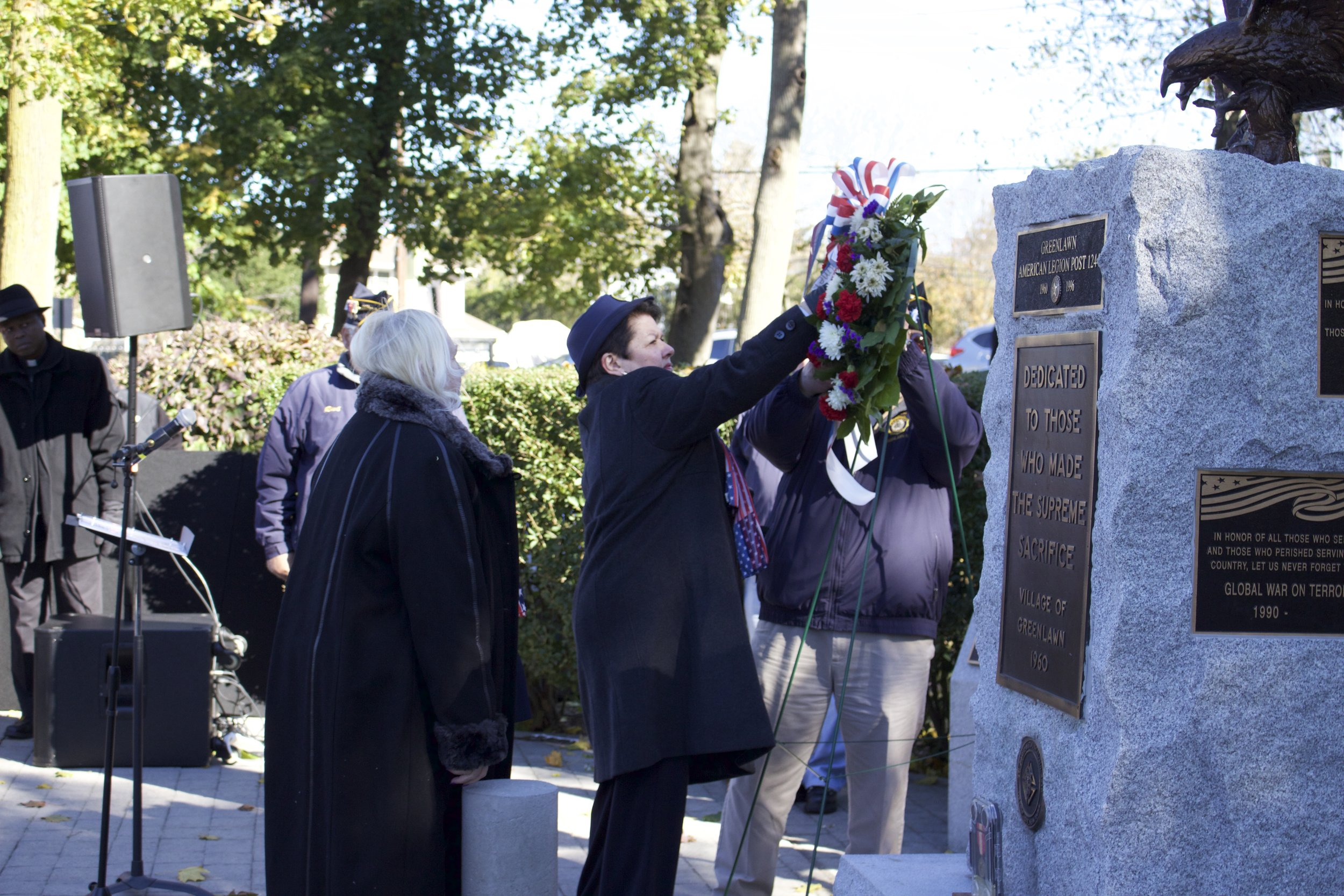 A member of Greenlawn Post 1244 Ladies Auxiliary places a wreath on the monument at Greenlawn Memorial Park.   Long Islander News Photo/Janee Law