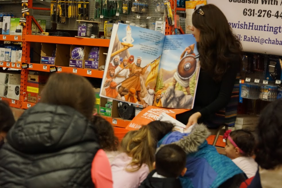 Children listen in during Jewish story time with Chaya Raskin, who read from a two-foot Chanukah book.  Photo Courtesy of Chabad of Huntington Village
