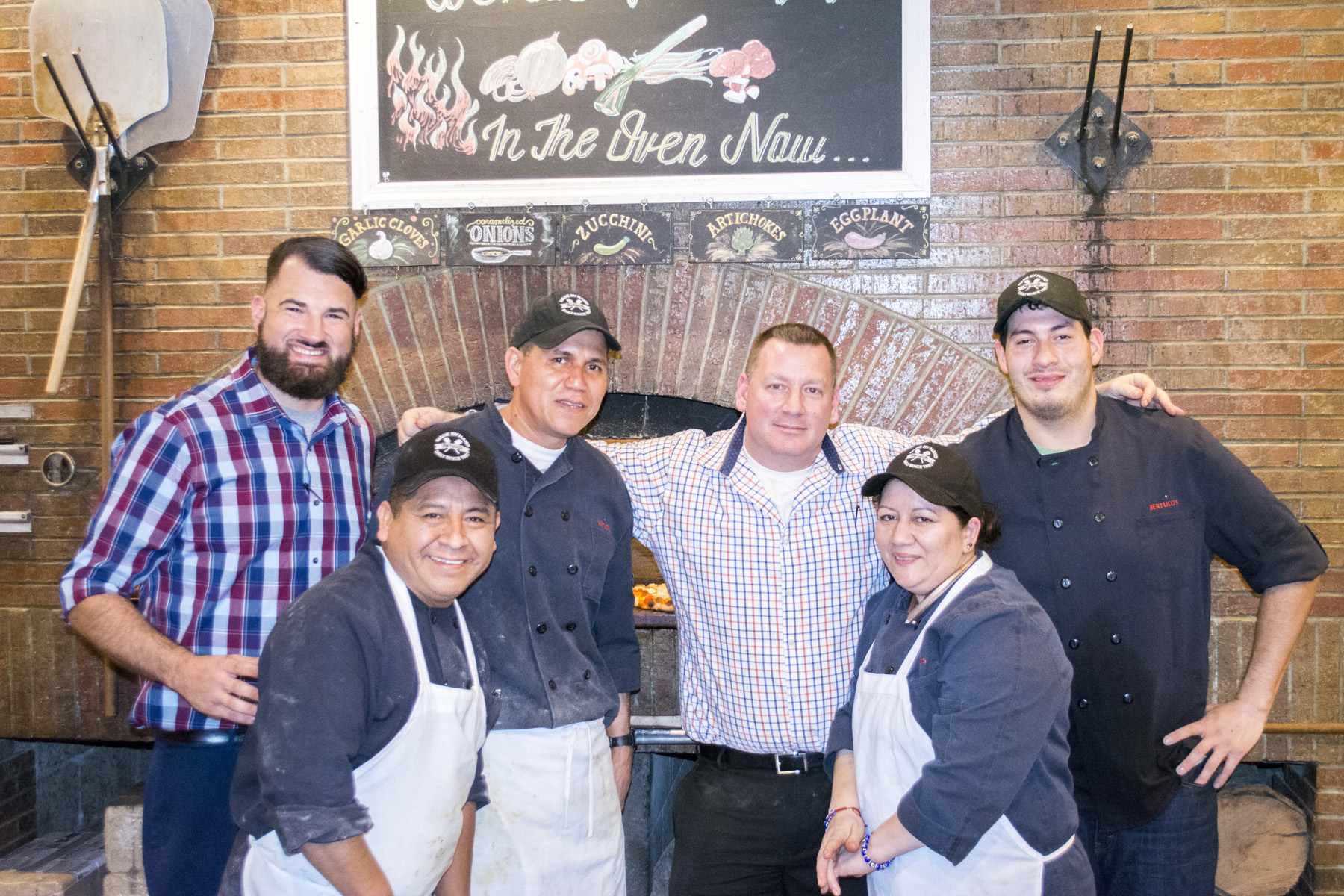 General Manager Corey Grossman, third from right, and the staff in front of the pizza oven at Bertucci's in Melville.   Long Islander News photos/Connor Beach