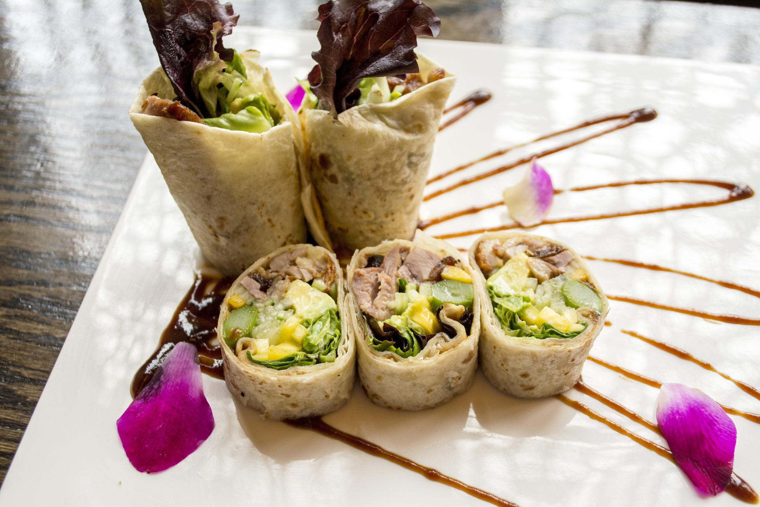 Duck Tacos include duck breast, mixed greens, avocado and cucumber wrapped in a tortilla with a honey mustard and hoisin sauce.