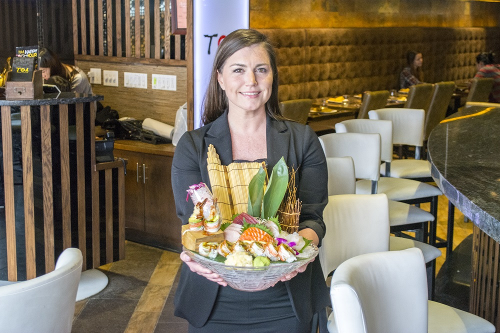 General manager Katie Moore, of Huntington, said the quality of food is what sets T.O.A. apart. She's presenting the restaurant's artfully plated Sushi and Sashimi Combo ($30).   (Long Islander News photos/Connor Beach)