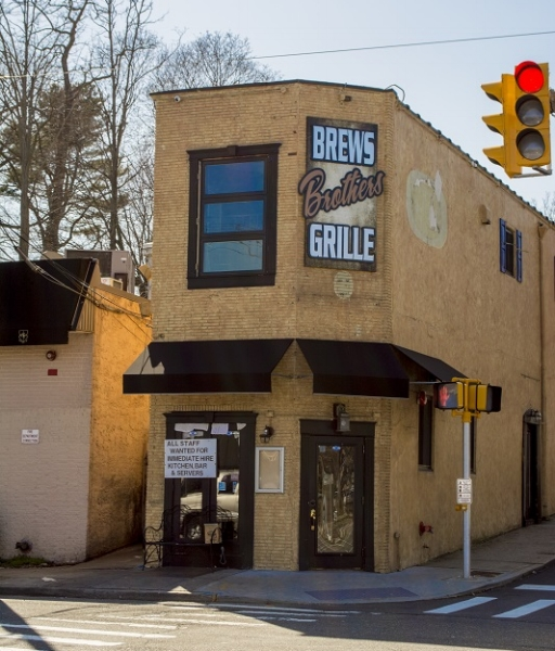 A new sign has popped up on this 69 Wall St. building, where brews Brothers Grille plans to open soon.   (Long Islander News photo/Peter Sloggatt)