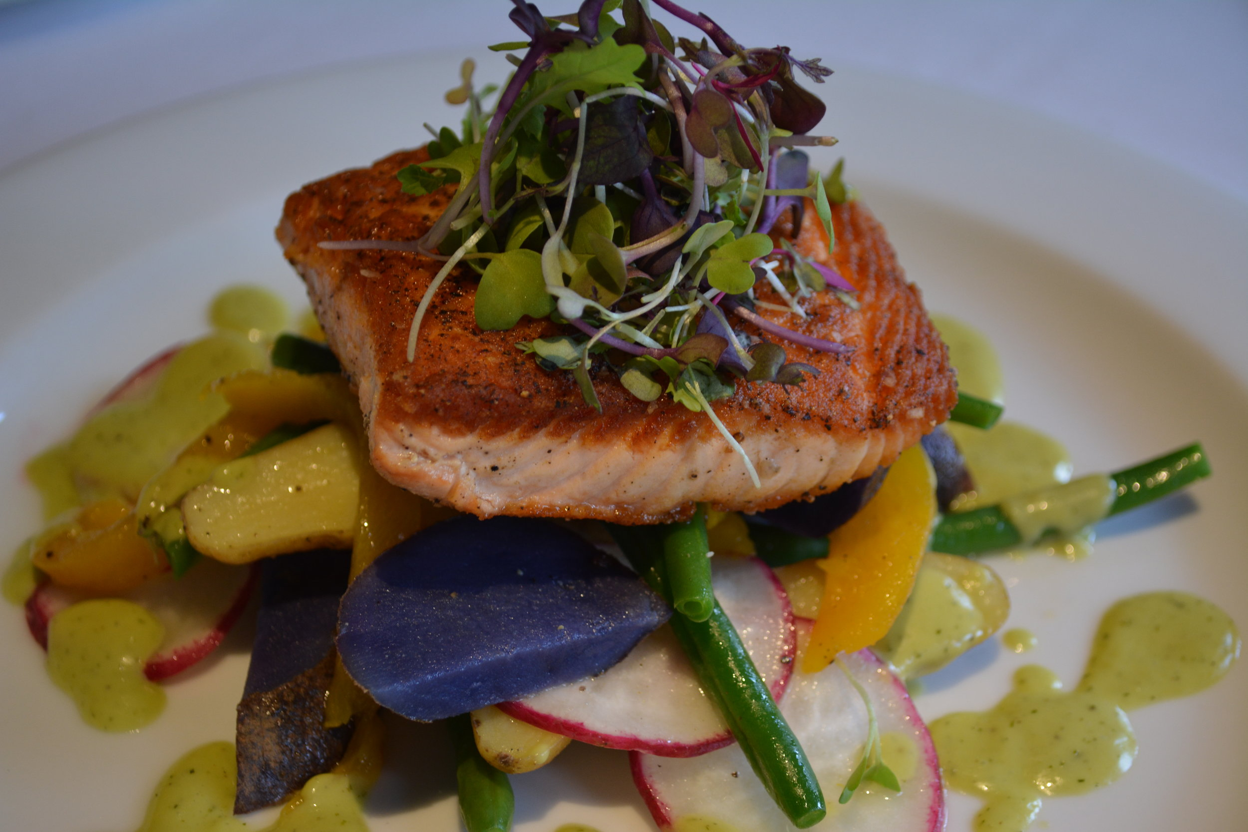 Salmon ($28) is served with a heirloom potato and string bean salad and a dill vinaigrette.
