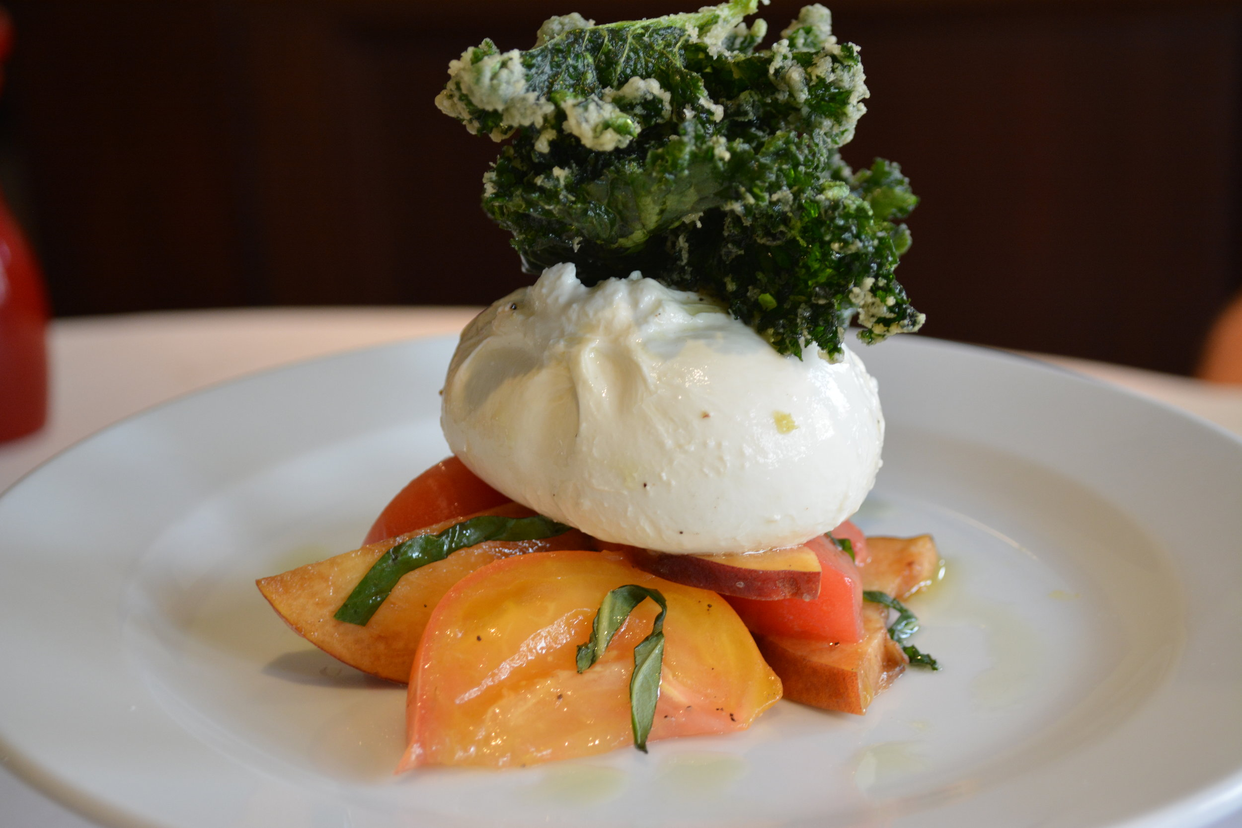 Rich, creamy Burrata ($15) with peach, heirloom tomato and crispy kale.