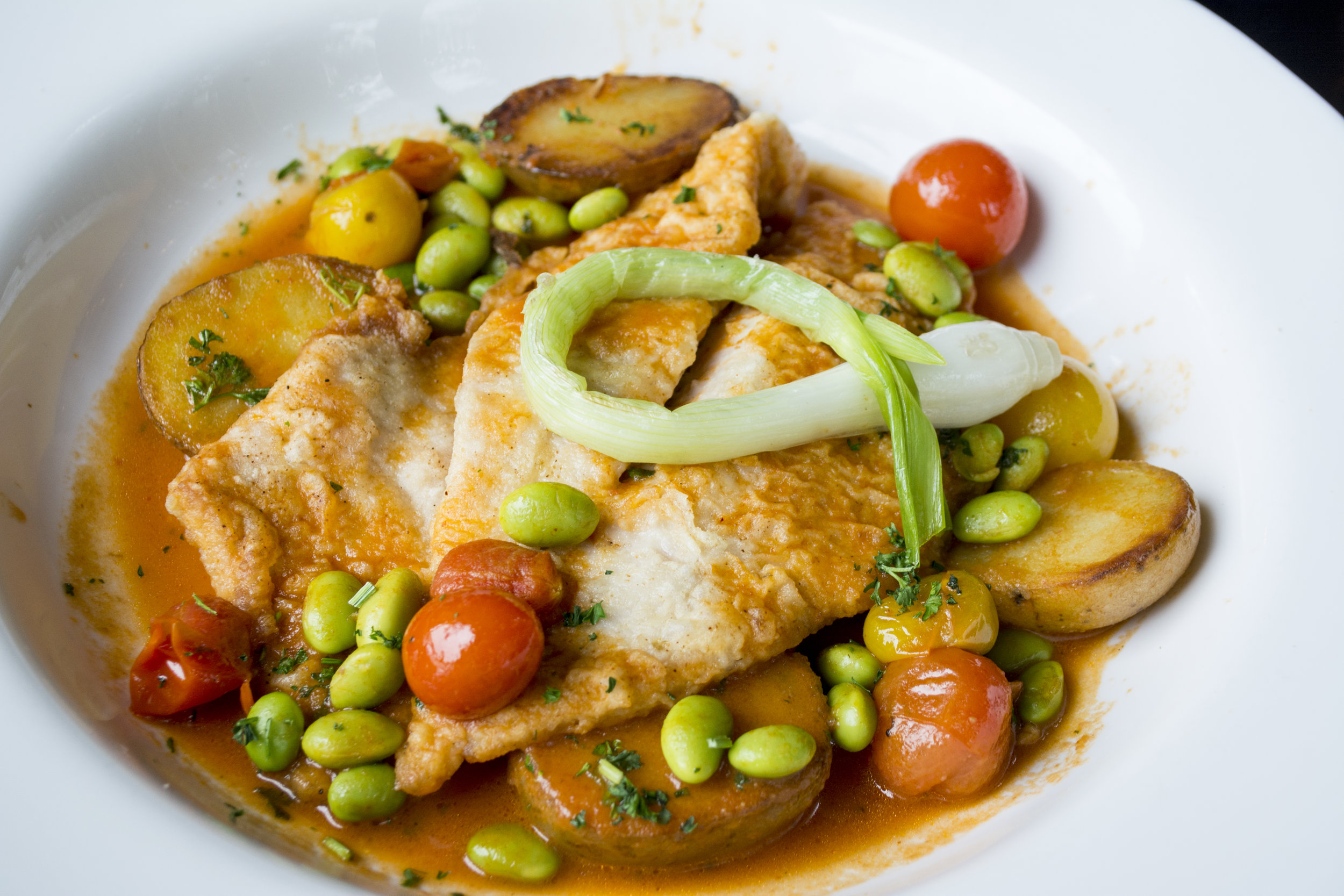 Local John Dory ($24) is served with yellow finn potatoes, baby spring onion, edamame and tomato broth.