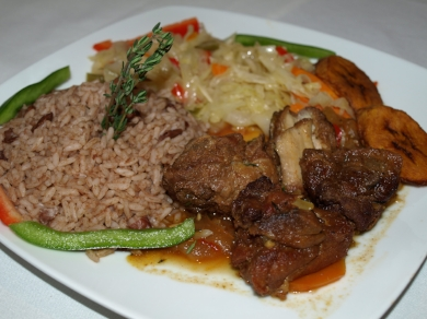 Specialties include a Stew Chicken Dinner ($9/small, $11/medium, $13/large) served over rice with fried plantains and vegetables.