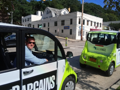 Mitch Hermann is at the wheel of one of Qwik Ride's distinctive 5-passenger golf carts during a press conference held to roll out the service in Northport Village.