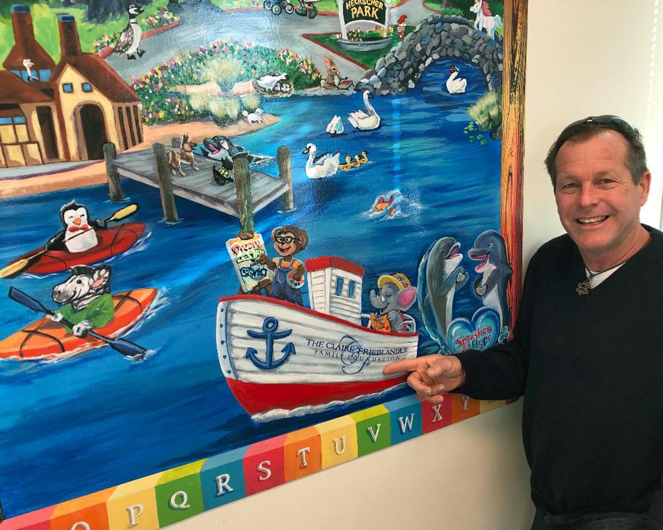 Splashes of Hope volunteer Jimmy Knapp shows off the mural recognizing its sponsor, the Claire Friedlander Foundation.