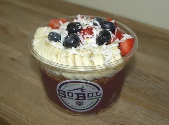 SoBol's signature açaí bowl has a blend of frozen açaí berries, strawberries, bananas and a splash of soy milk, topped with granola, bananas, strawberries, blueberries, shredded coconut, and drizzled honey.