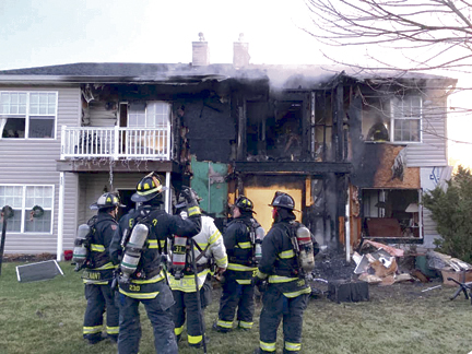 Firefighters assess the damage after a fire ripped through a condo complex in Melville on Dec. 27.  Photo/Melville FD