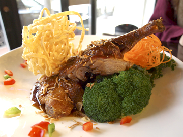 Tamarind Honey Duck ($24.94) is plated with broccoli and crispy noodle.