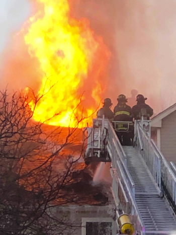 Firefighters attack the Avalon Court complex fire from a bucket truck.  Photo/Melville FD
