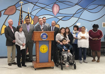 Senator Jim Gaughran, at podium, joins, from left, Legislator Tom Donnelly, Debbie Rimler, Legislator William Spencer, Supervisor Chad Lupinacci, Assemblyman Stern Stern, Mileny and her son Diego, Lily Sovuoj, Maria Georgiou, Nelis, Angela Williams at the Tri CYA in Huntington to announce funding for the C.A.S.T program in the state budget.  Photo/Office of Sen. Jim Gaughran