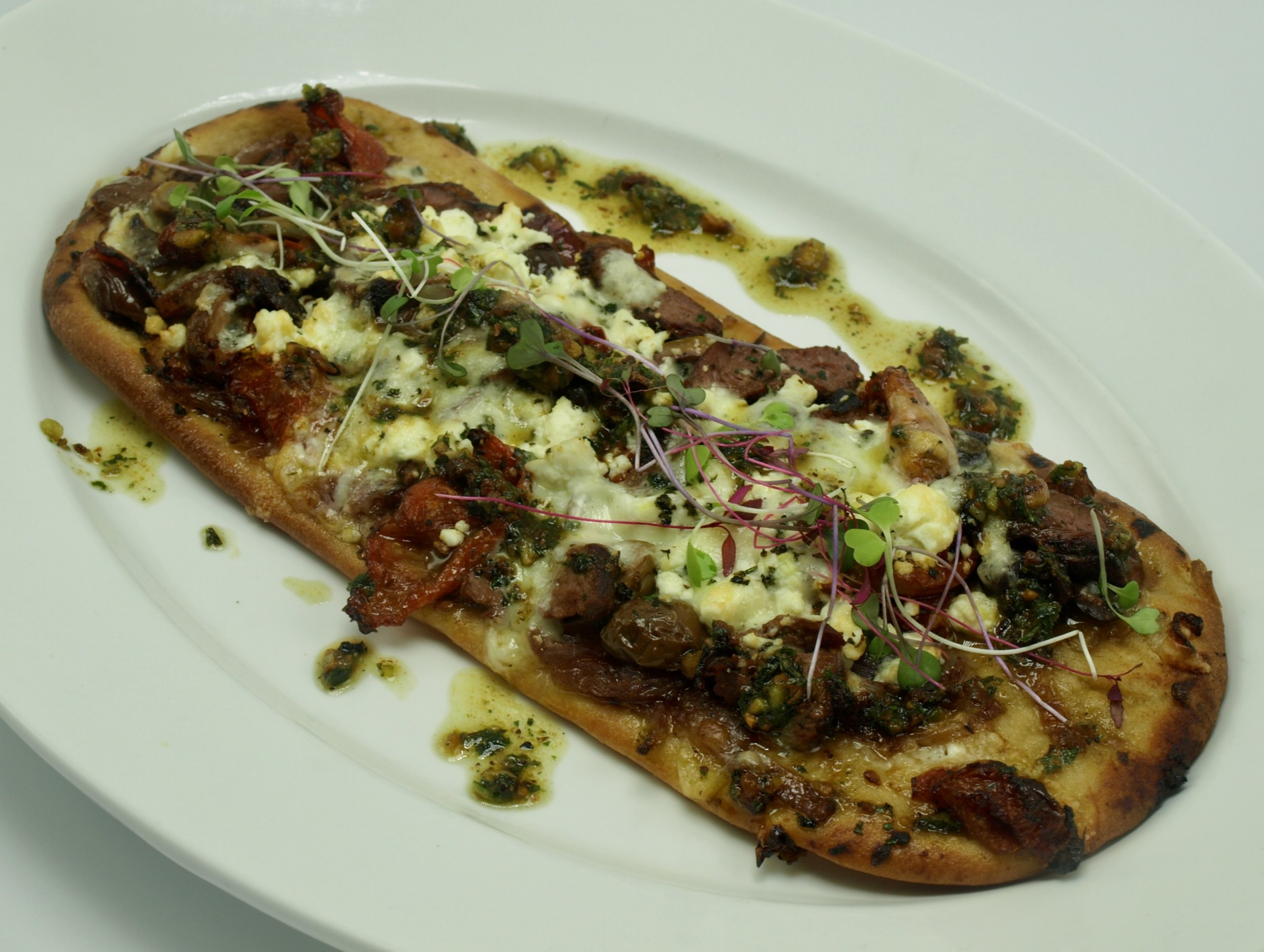 Mediterranean Flatbread with tenderloin, caramelized red onion, kalamata olives, cured tomato, feta, fontina and toasted pistachio pesto.