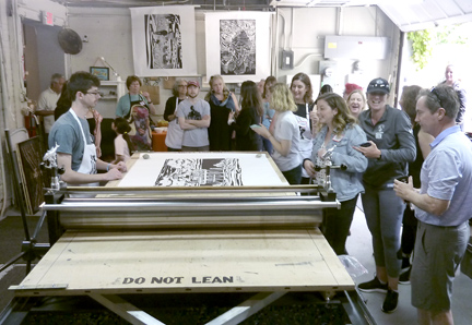 Artists gathered around the Big Ink mobile press.