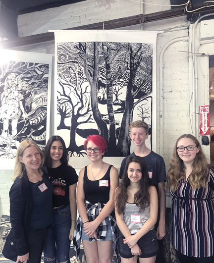 Northport High School art teacher Constance Wolf and students Emma Halperin, Kat Schorn, Eli Dalton, Olivia deFeo and Elle Vezzi in front of the students' print of trees.