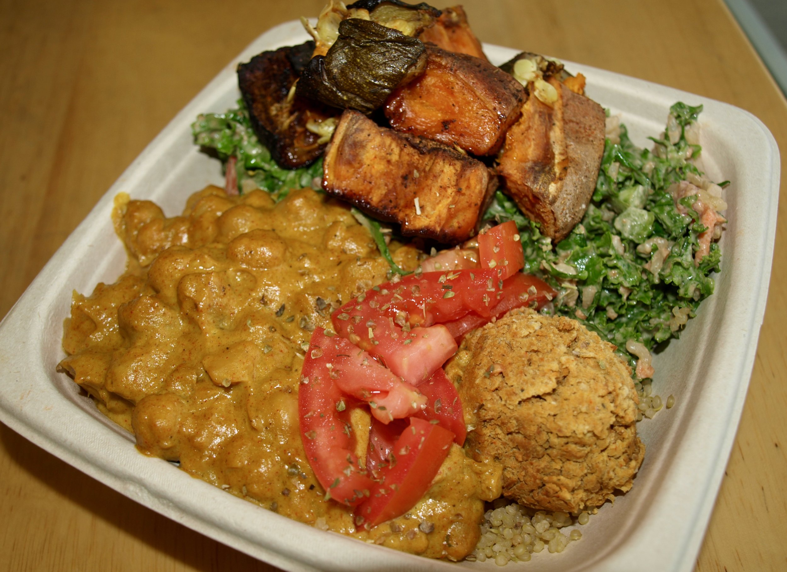 Half & half of Southern charm (kale, cilantro, brown rice, tomato, red onion, carrots, topped with roasted veggies, and masala bowl (chickpea masala, tomato, falafel, sunflower tahini).