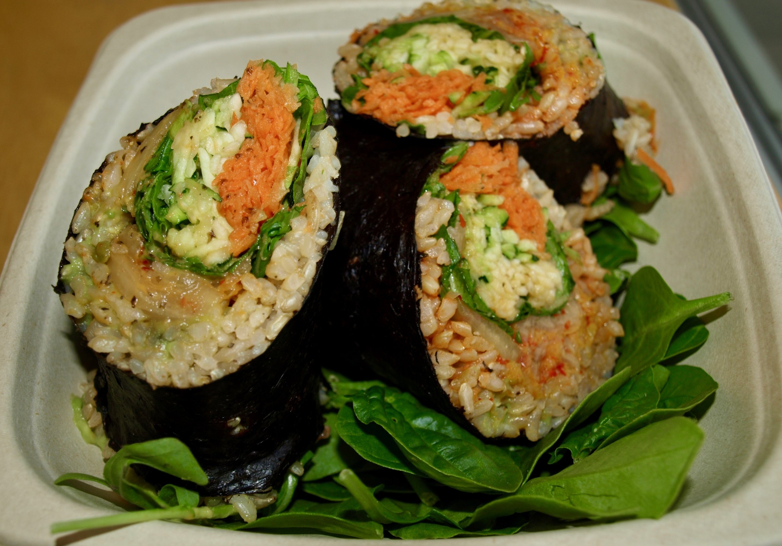The zen roll, with spicy kimchi, brown rice, avocado mash, zucchini noodles, arugula, carrots, and thai dressing.