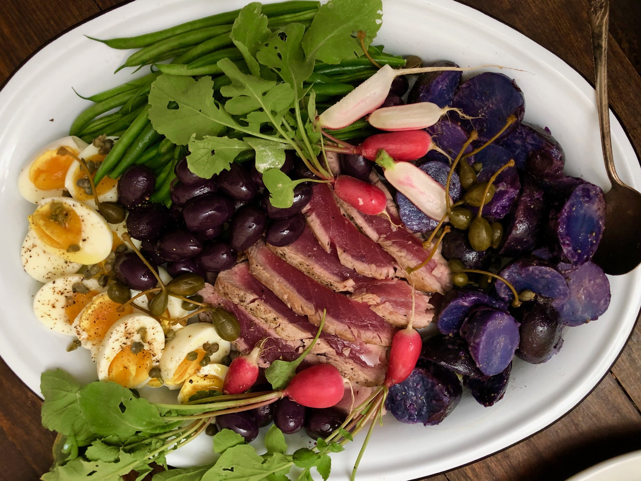 Seared tuna niçoise platter is a colorful combination of radish, string beansn potatoes and hard boiled eggs.