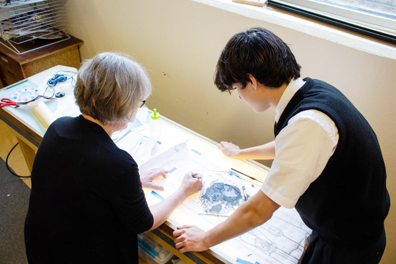 Art teacher Jennifer Baldwin-Schafer and student Matthew Meberg work on the stained glass design. Each of the 39 custom windows pays tribute to the school's patron families.