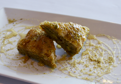 Honey-drizzled Baklava with walnut and pistachio     is topped with house dressing.