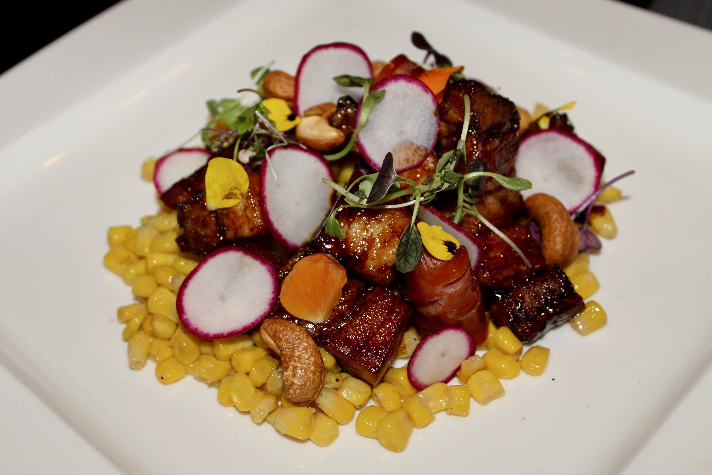 Braised Pork with pork sausage and radishes on a bed of sweet corn.