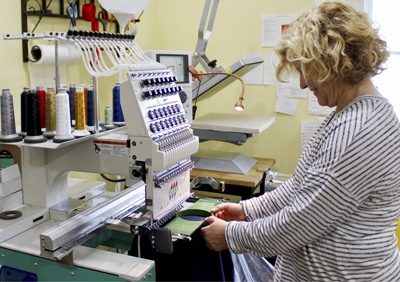 Terri Ehrman places a piece of fabric in the hoop of the embroidery machine at her business, Interthread Embroidery.