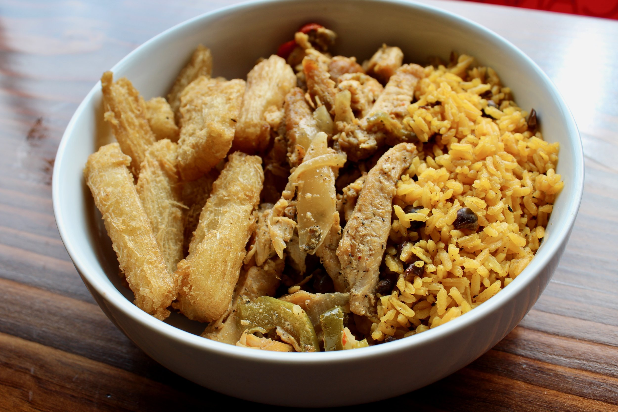 Cana bowl with grilled chicken, yellow rice and peas, and fried yucca.