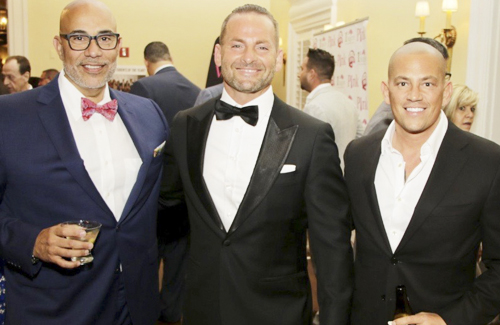 "Lloyd Neck resident Asaf German's ""Racing to a Cure"" event held at Ferrari Maserati of Long Island raised over $70,000. Pedro Velez, left, and Christopher Chiarenza, right, were among more than 400 guests who joined German, center, at the event."