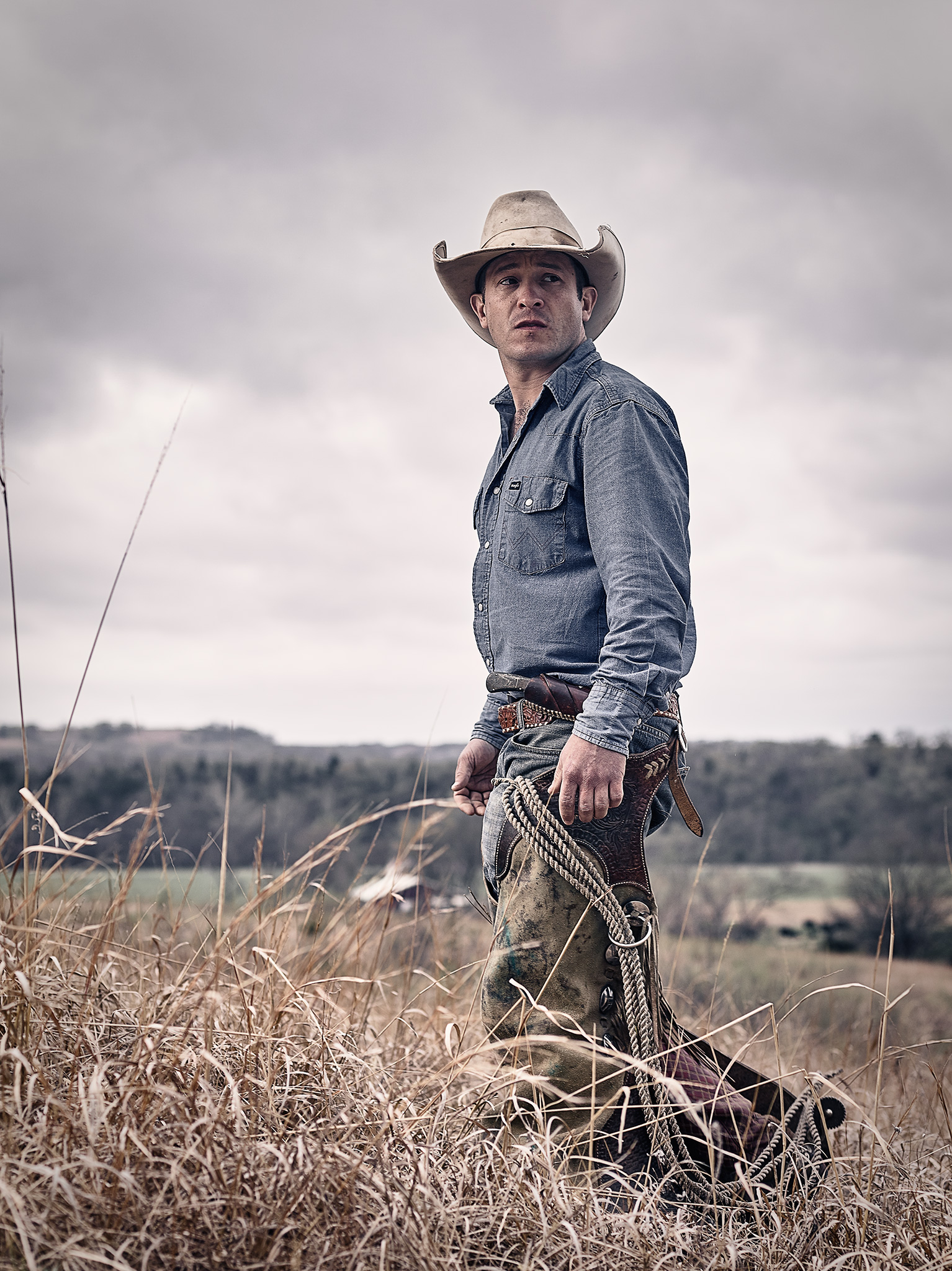 A Flint Hills cowboy walking through a pasture in the Fall.