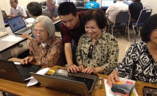 Youth teaching seniors how to use computers and the internet.